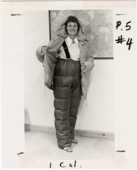 A woman stands in snow pants, suspenders, and a puffy jacket.