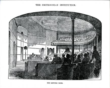 Lecture Hall looking toward the stage. A man is demonstrating an experiment to an audience seated in