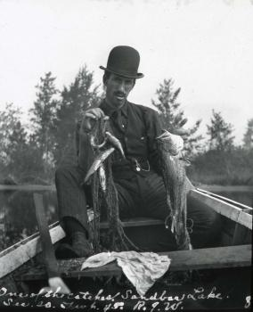 A man in a suit and hat stares directly at the camera, holding a fish and a net. Trees and a body of