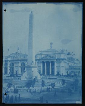 People walk around an obelisk monument in an area in front of a large. The cyanotype is tinted blue.