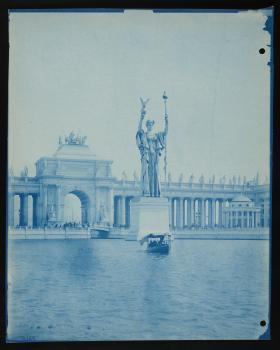Blue-tinted cyanotype of a statue in the middle of a lake. A large, beautiful building is in the bac