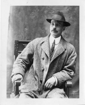 Black-and-white photograph of a man wearing a hat and coat sitting in a chair.