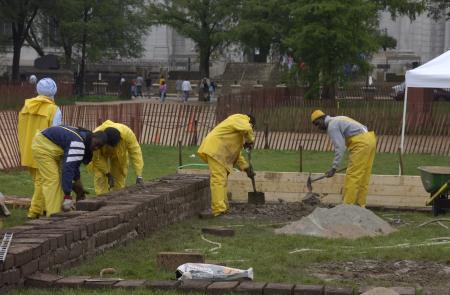 Color photo of workers in yellow rain gear laying a brick foundation outside in rainy weather.