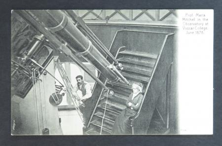 B & W image of a women sitting on a small case, and a man on a latter, next to a large telescope.