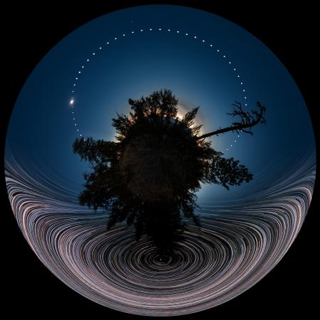 Circular image of eclipse with stars trailing in the sky.