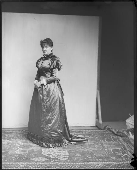 Portrait of woman, standing in front of a backdrop, wearing a long dress with large sleeves.