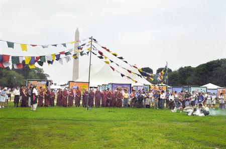 Color photograph of a large group of Tibetans in traditional clothing, standing outside on the Natio
