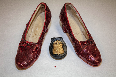 Two ruby slippers with an FBI badge and single red sequin in between the slippers.