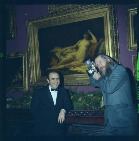A man stands and leans next to a painting. Another man holds a camera to his eye and points the came
