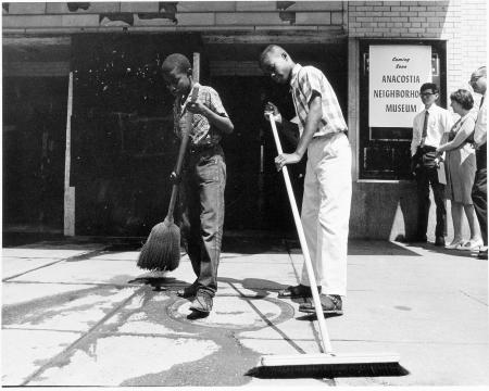 Black and white photograph of two young boys sweeping sidewalk in front of museum entrance.