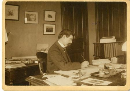 Robert Ridgway sits writing at his desk in his office located in the United States National Museum,