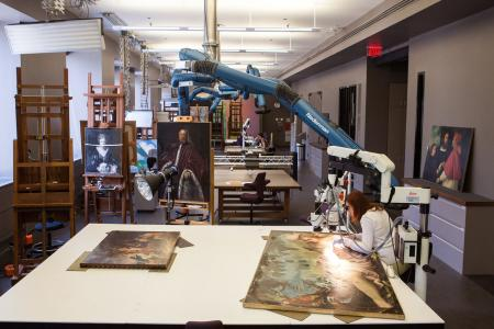 A female conservator looks through a microscope as she conserves a large painting.