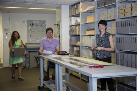 Color photo of three staff members standing in the collections processing lab