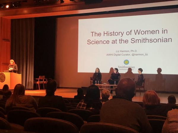 Dr. Liz Harmon stands at a podium, while three women sit in chairs on the stage. A talk, titled