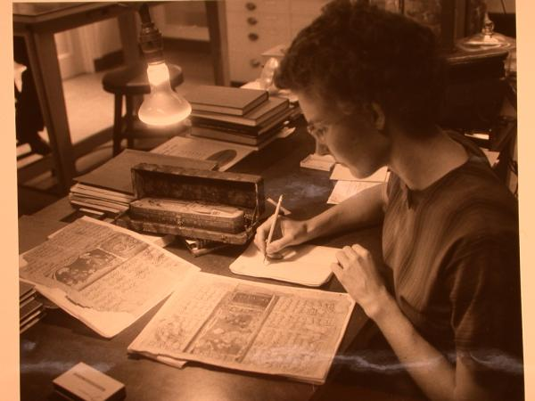 A woman sits at a table and takes notes as she analyzes an old text.