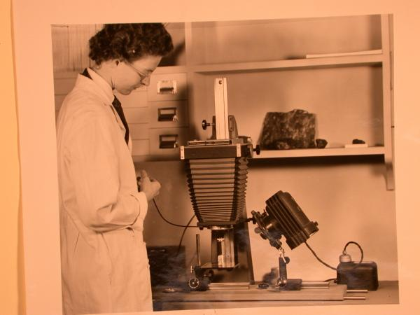 A woman wearing glasses and a lab coat takes a photo of a museum object in a laboratory.