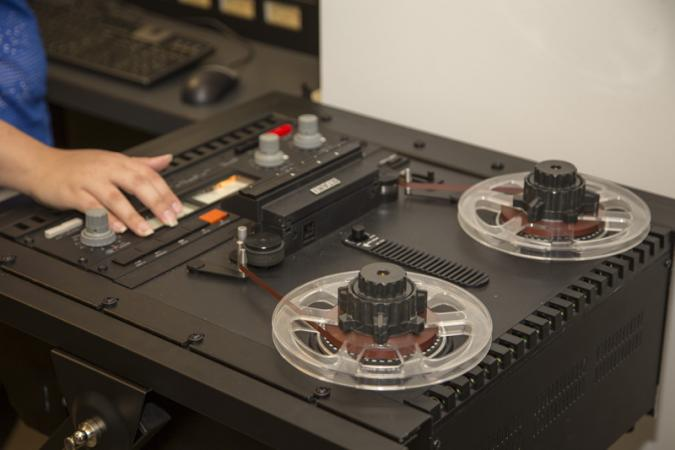 Kira Sobers works on an audio reel-to-reel tape recorder. It has two tape wheels and many buttons.