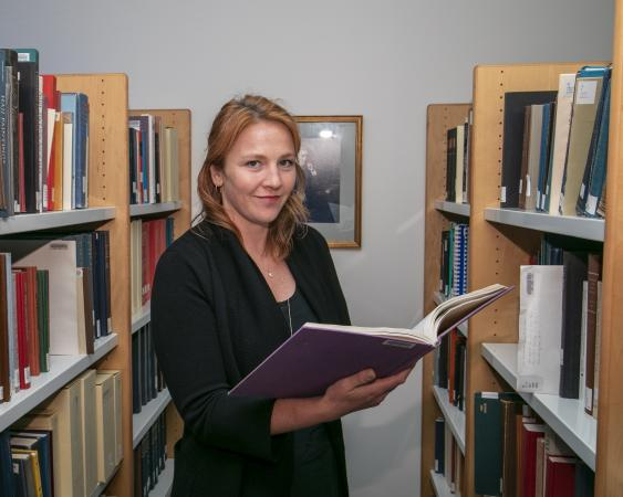 A woman stands in between stacks of books. She is holding open a large book and looking toward the c