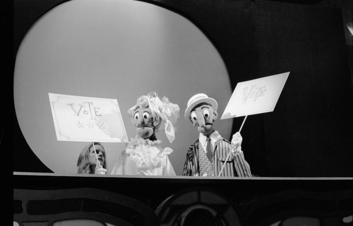 Two puppets holding up posters that read: Vote.