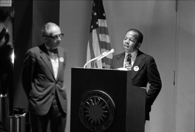 Lewis speaks at a podium.