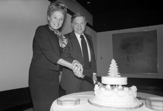 Lerner puts his hands over Rosenberg's as the two hold a knife and cut into a cake with a Christmas