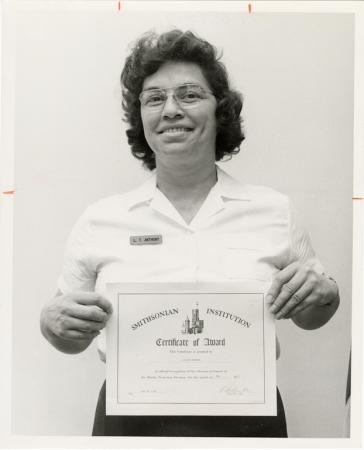 "A woman in a white polo holds up a certificate that reads: ""Smithsonian Institution Certificate of A"