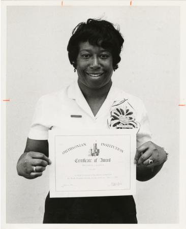 "A woman wearing a white polo and a badge smiles at the camera and holds a certificate that reads: ""S"