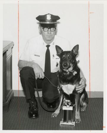 "Portrait of Officer Kenneth Brewster and SI Guard-dog ""John"" with Competition Trophy"