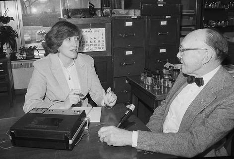 A woman interviewing a man at a table with a recorder in between them.