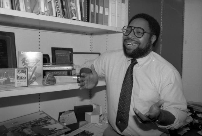 Lonnie G. Bunch III stands in an office in front of a cluttered bookshelf.