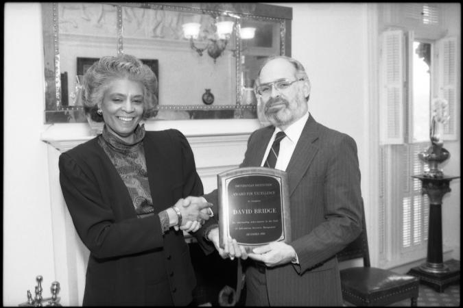 A woman presents an award to a man. They are shaking hands.