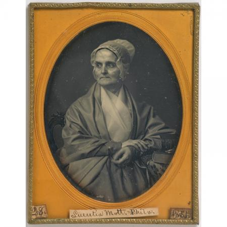 Portrait of a woman sitting. She is wearing a bonnet. The image is framed in an orange oval inside a
