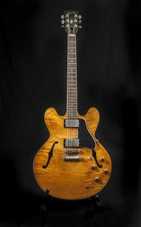 A six-string, semi-acoustic guitar has a light brown maple body photographed on a black background.