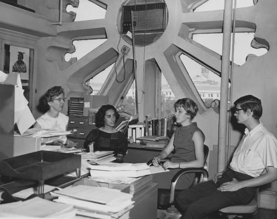 One man and three women sit in a group near a large window with many cutouts.