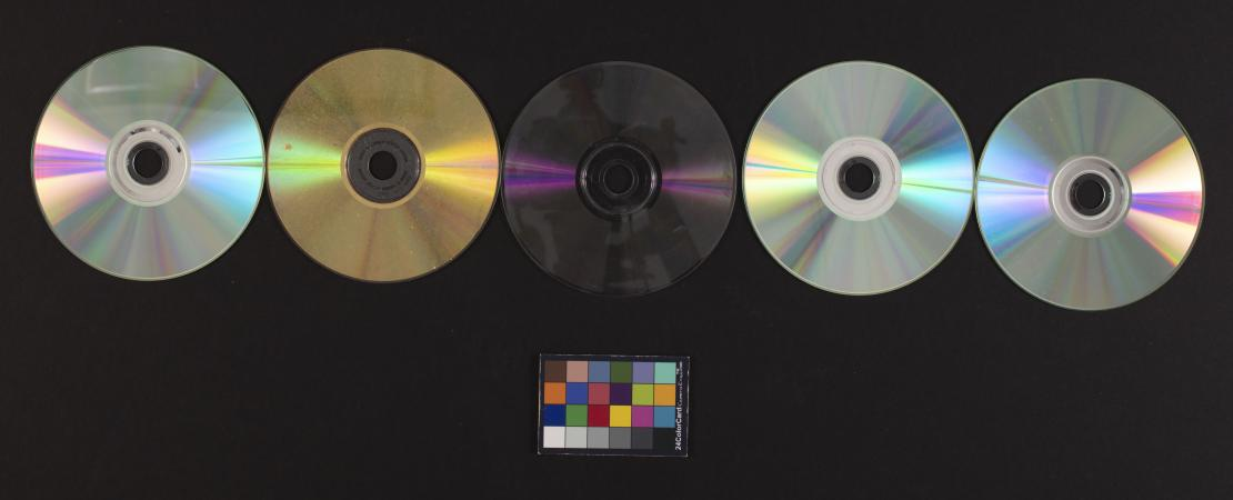 Five CDs and a color card against a black background.