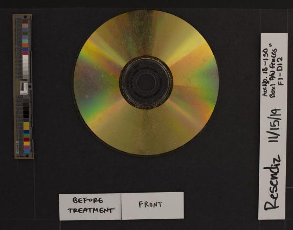 A dusty gold CD surrounded by a measurement scale and color card and object information labels.