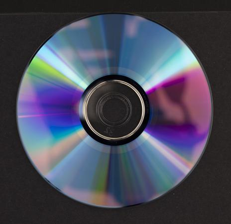 The iridescent reverse side of a DVD has an amorphous shadow that is a reflection from the camera.