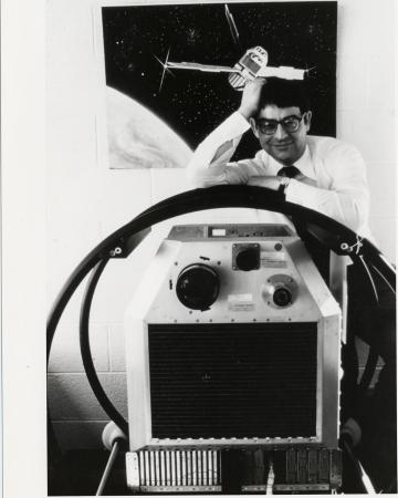 A man leans against a machine. A poster of space is in the background.