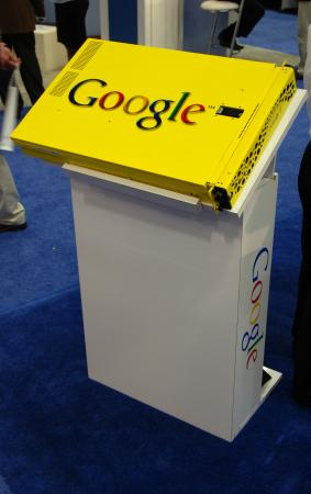 "Image of a bright yellow box with the word ""Google"" in color. It is on a small podium-like white box"