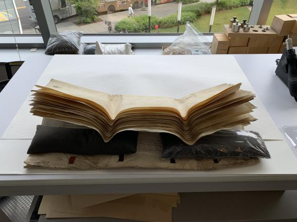 A parchment document, folded in half horizontally, rests atop white cotton blotters, and is prevente