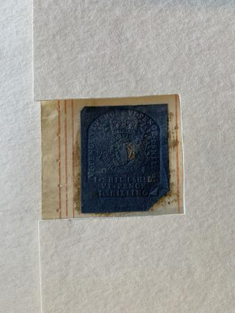 : A rectangular window cut from one edge of a white cotton blotter reveals a blue embossed tax stamp