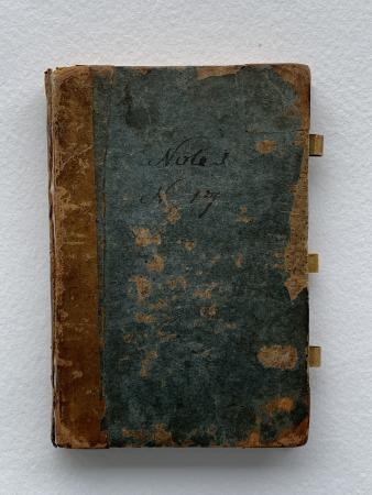 "View of a leather-bound book cover with three loop holes at the edge. The cover is damaged and ""note"