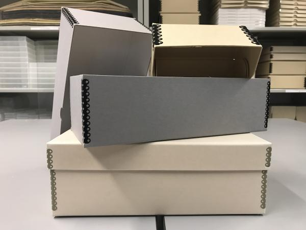 Acid-free boxes in various shapes and sizes on a table.