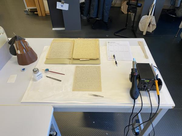 The damaged papers are on a desk next to conservation tools.