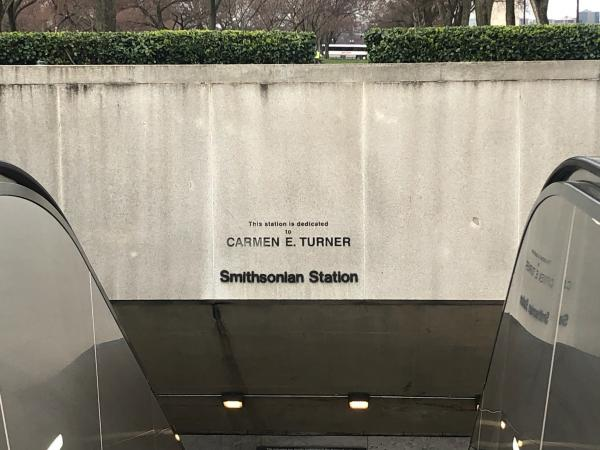 "Photograph of the memorial sign, which reads: The station is dedicated to Carmen E. Turner."" View fr"