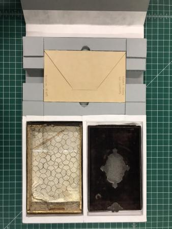 Image of a flat box that includes spaces for an envelope and two other objects.