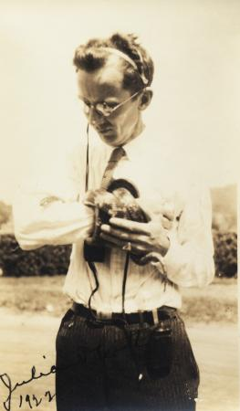 A person wearing wires around their head holds a snake wrapped around one arm.
