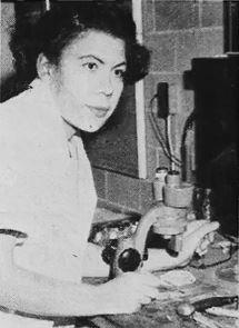 Black and white photo of a young Margaret Collins sitting at a lab bench with a microscope in front