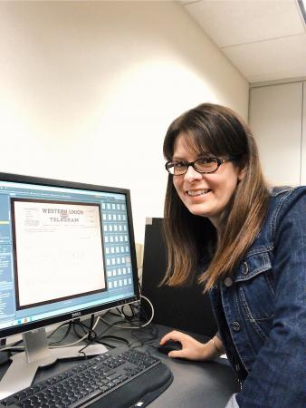 A woman wearing glasses and a denim jacket posed for a picture next to a computer screen. She has on