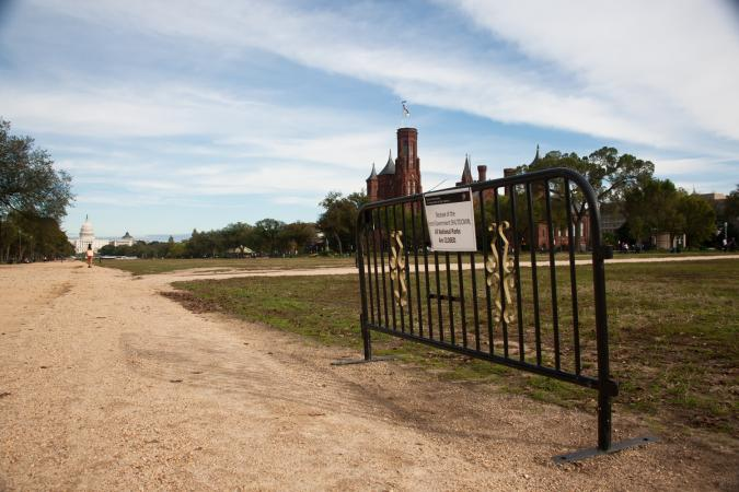 A small gate with a sign about the government shutdown stands on the National Mall. The Smithsonian